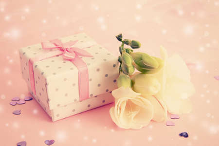 engagement party: Beautiful little gift box and freesia flower on pink background