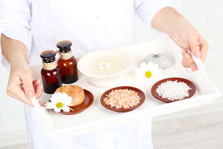 Beauty therapist holding tray of spa treatments, close-up Stock Photo