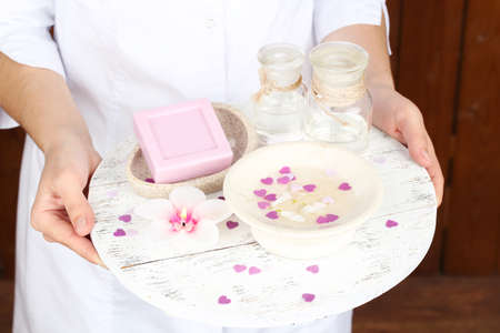 beauty therapist: Beauty therapist holding tray of spa treatments, close-up, on wooden wall background Stock Photo