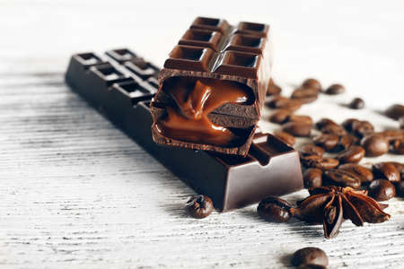 chocolate chips: Stuffed chocolate with coffee beans on wooden table, closeup Stock Photo