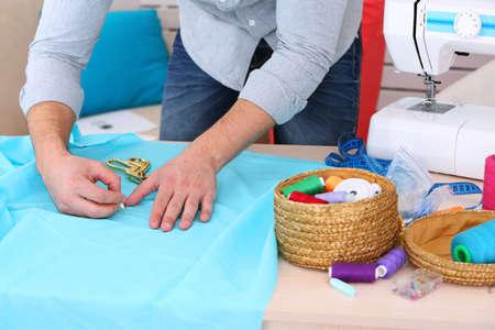 dressmaker: Male dressmaker cut fabric on table