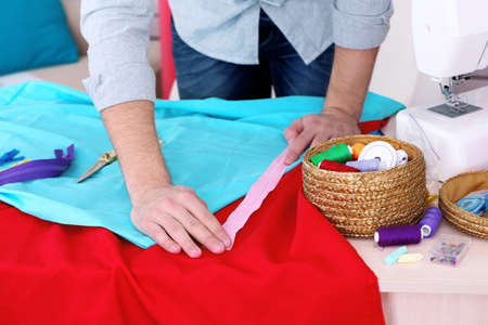 dressmaker: Male dressmaker tailor fabric on table