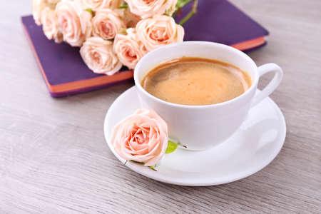 planta de cafe: rosas frescas con el diario y la taza de café sobre fondo de madera
