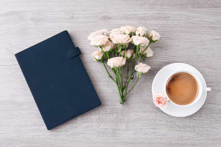 Fresh roses with diary and cup of coffee on wooden table, top view
