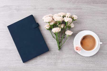 bouquet fleurs: Roses fraîches avec agenda et tasse de café sur la table en bois, vue de dessus Banque d'images