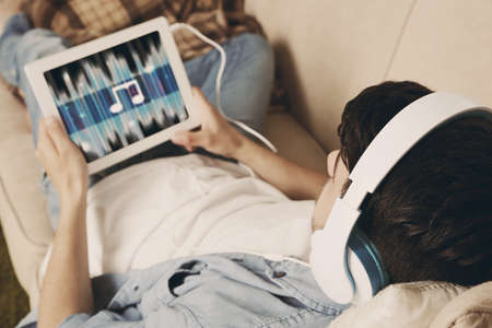 listening music: Handsome young man lying on sofa and listening to music in room