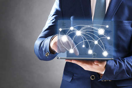 connection: Businessman holding tablet-pc with social network structure Stock Photo