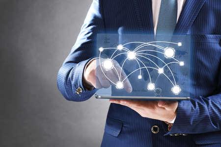 conexiones: El hombre de negocios que sostiene la tablilla-PC con estructura de red social Foto de archivo