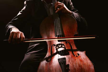 cello: Man playing on cello on dark background
