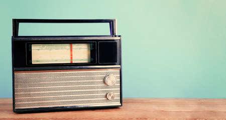 shortwave: Retro radio on wooden table on turquoise background