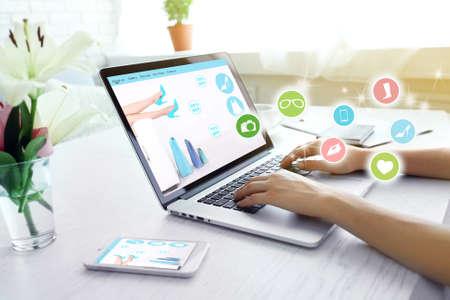 Mujer que usa la computadora portátil en lugar de trabajo. las compras en línea