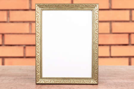 modern frame: Old empty frame standing on table on brick wall background Stock Photo