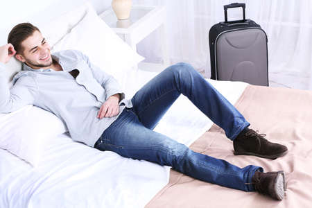 Tired man resting on bed in room Stock Photo