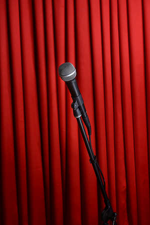 Microphone on stand on red curtain background Фото со стока