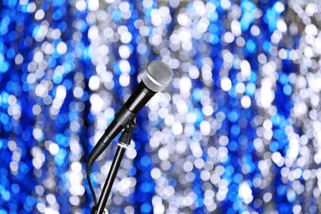 amplified: Microphone on stand on blue background Stock Photo