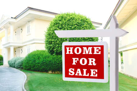 Real estate sign in front of new house for sale Stock Photo