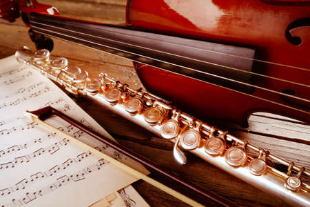 silver flute: Flute and violin with music notes on wooden table close up Stock Photo