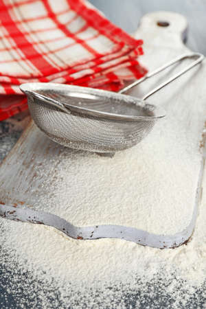 sieve: Sifting flour through sieve on wooden table, closeup
