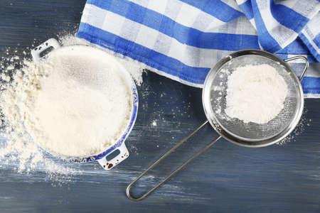 Sifting flour through sieve on wooden table, closeup
