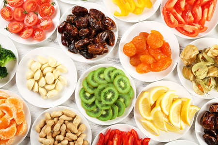 frutos secos: Los diferentes productos en los platillos en la mesa de madera, vista desde arriba