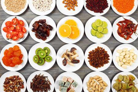 frutas secas: Los diferentes productos en los platillos en la mesa de madera, vista desde arriba