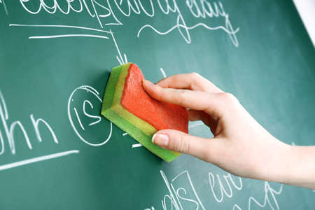 Teacher hand wiping off sentences from blackboard background Stock Photo
