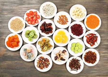 legumbres secas: Los diferentes productos en los platillos en la mesa de madera, vista desde arriba
