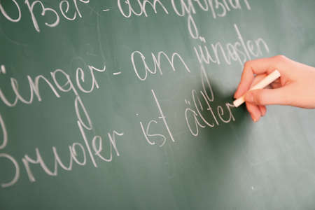 syntactic: Teacher hand writing grammar sentences on blackboard background