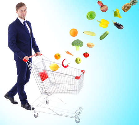 Young man pushing  shopping cart with different food on blue background Stock Photo