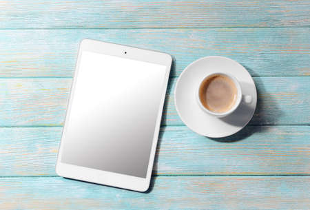 digital device: Cup of coffee and tablet on wooden table. Preparing for travel,reservation ticket