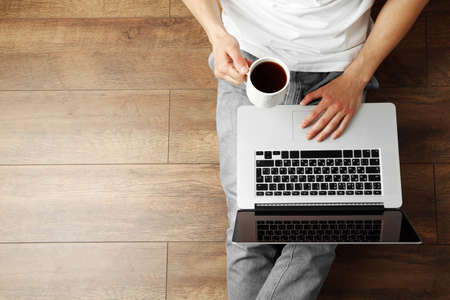 Young man sitting on floor with laptop and cup of coffee in room 스톡 콘텐츠