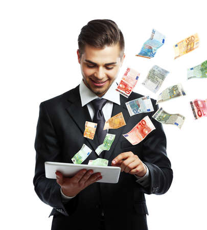 Elegant man in suit holding tablet with money fly out of it Reklamní fotografie - 95152675