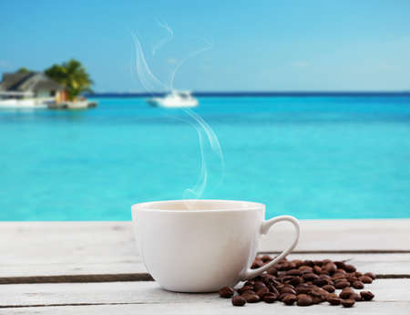 Cup of coffee on table on sea background