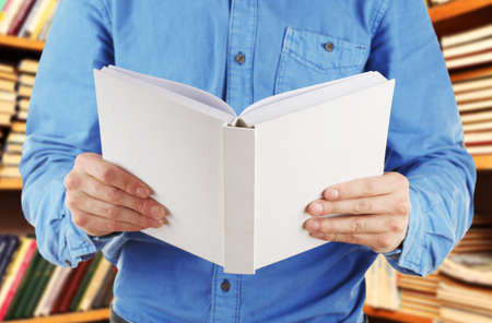 book shelves: Male hands holding open book on bookshelves background