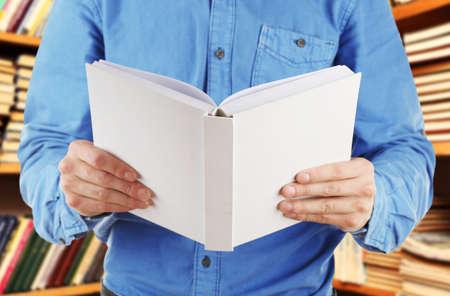 libro abierto: Manos masculinas que sostienen el libro abierto en las estanterías de fondo