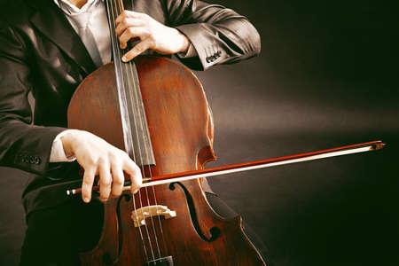 dark brown: Man playing on cello on dark background