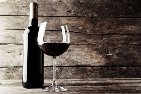 vino: Botella de vino tinto y un vaso en la mesa de madera, blanco y negro estilización retro