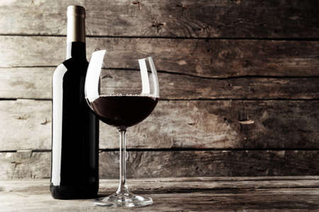 Bottle of red wine and a glass on wooden table , black and white retro stylization