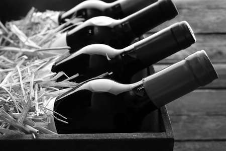 glass bottles: Box with straw and wine bottles,  black and white retro stylization Stock Photo