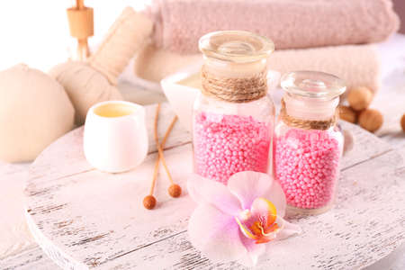 wooden color: Glass bottles with color spa sea salt on wooden table, closeup