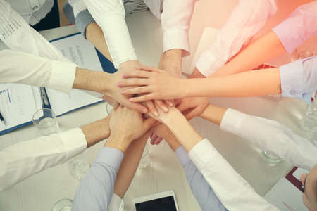 United hands of business team on workspace background top view