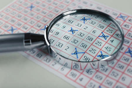analyzing: Analyzing lottery ticket with magnifier, closeup