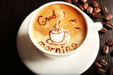 Cup of latte art coffee with grains, closeup Standard-Bild