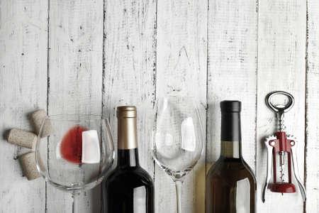 bodegas: Botellas de vino, vidrio y sacacorchos en mesa de madera, blanco y negro estilización retro Foto de archivo