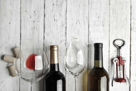 Bottles of wine, glass and corkscrew on wooden table,  black and white retro stylization