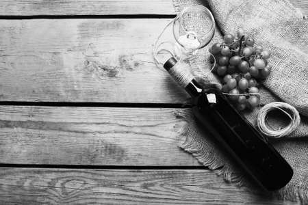 stylization: Bottle of wine and grape on wooden table,  black and white retro stylization