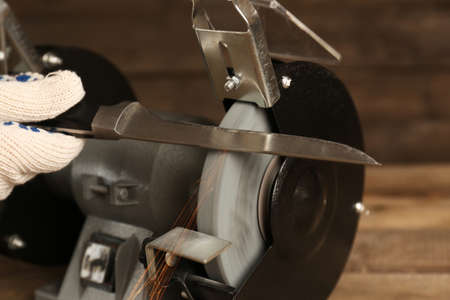sharpening process: Knife sharpener and hand with blade on wooden table, closeup Stock Photo