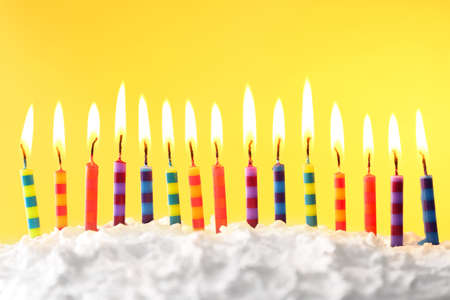 색상 배경에 촛불 생일 케이크