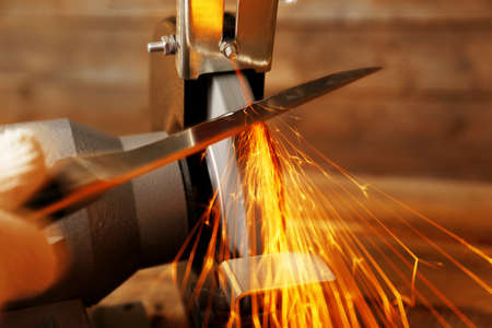Messenslijper en hand met mes op houten tafel, close-up