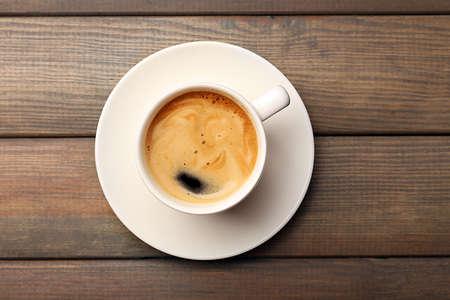 filiżanka kawy: Filiżanka kawy na drewnianym stole, widok z góry